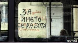 "A woman sits in a bus as it passes a graffiti that reads ""It's all about the name"" in Skopje March 21, 2011"