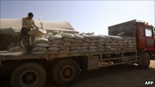 Worker loading cement bags on a truck