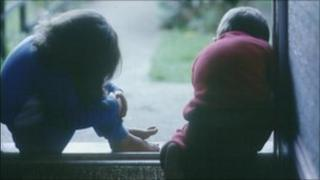 Young girl and boy sat in doorway