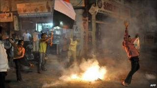 Indian cricket fans celebrates with fireworks as they wave flags in a street of Hyderabad on March 30, 2011