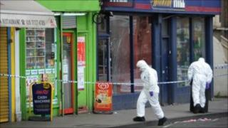 Forensic officers examine the scene in Brixton, south east London where a five year old girl was shot