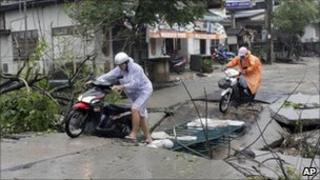Tourists make their way on a damaged road on Koh Samui island after heavy storms
