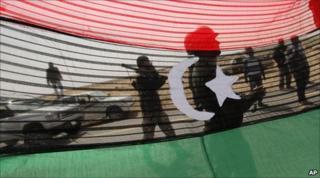 Rebels seen through a pre-Gaddafi flag outside al-Agila, Libya. 30 March 2011
