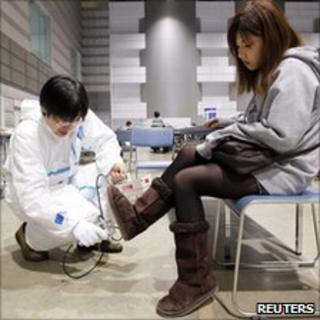 A Japanese woman is checked for radiation