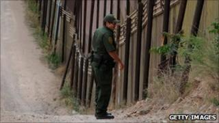 US border patrol agent at the US-Mexico border fence