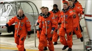 Lisa Nowak, second from left, and other astronauts in flight gear on a tarmac