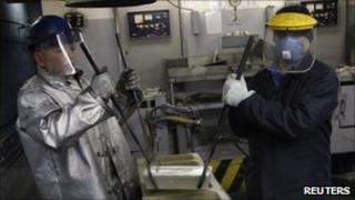 Workers remove an ingot of 99.99 percent pure silver at the Krastsvetmet nonferrous metals plant in Russia's Siberian city of Krasnoyarsk