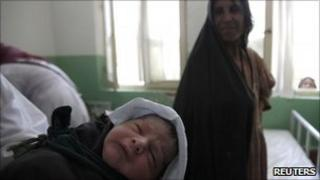 A midwife holds up a baby as the mother looks on at a hospital in the Afghan city of Farah in this August 10, 2009 file photo.