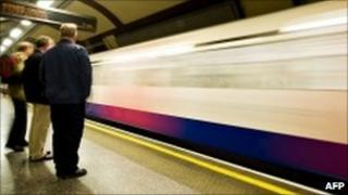 Commuters wait on a platform for a Piccadilly Line underground train