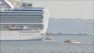 Tenders travel to and from a cruise ship moored off Guernsey