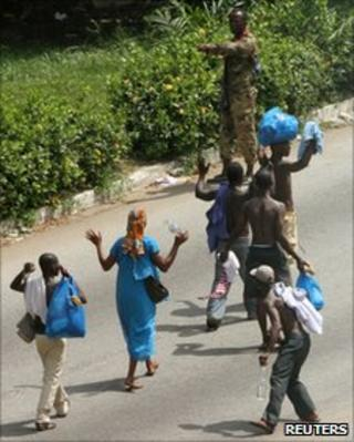 Civilians raise their hands as they walk past a pro-Gbagbo soldier in Abidjan on 3 April 2011