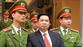 A handout photo taken and released on April 4, 2011 by the Vietnam News Agency shows Cu Huy Ha Vu, 53, as he is escorted by policemen from his trial at the Hanoi People's Courthouse