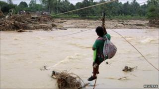 A villager uses ropes and buoys to cross a broken bridge damaged by a flash flood in Nakhon Si Thammarat province, south of Bangkok