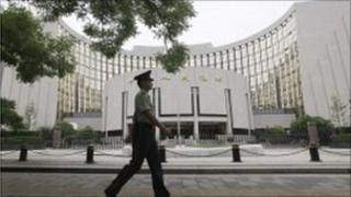 Guard walks past the People's Bank of China building