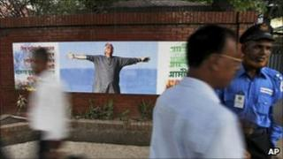 Bangladeshis walk past a billboard showing Nobel laureate Muhammad Yunus