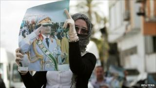 A supporter displays a picture of Libyan leader Muammar Gaddafi during an anti-coalition protest in Tripoli, 2 April 2011