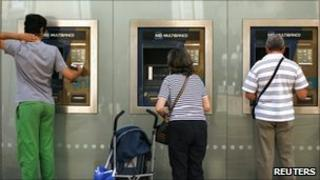People using ATMs in Lisbon