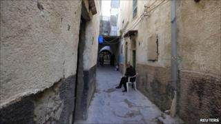 A Libyan man sits by his house along one of the narrow streets in the old city of Tripoli, 6 April 2011.