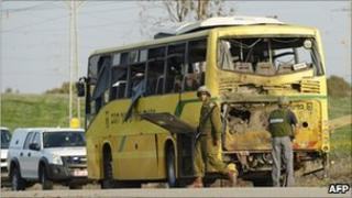 Israeli soldiers stand by a school bus hit by Gaza militants, 7 April