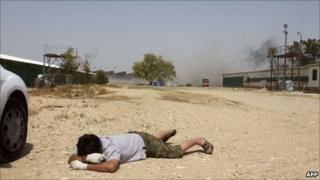 A foreign worker lies on the ground as mortar shells hit the southern Israeli kibbutz of Nir Oz, 8 April