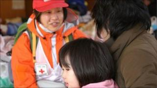 Member of the Japanese Red Cross Society helping people at evacuation centre. Picture supplied by British Red Cross.