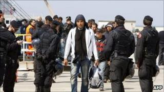 Tunisian immigrants disembark from a ferry boat during evacuation from Lampedusa to a reception centre in Manduria on April 1, 2011