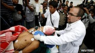 A man on a stretcher is taken to hospital after being injured during protests in Arequipa on 7 April 2011