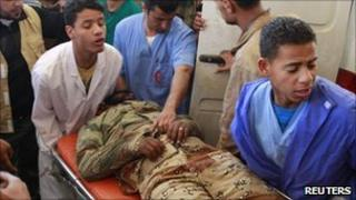 Medical staff tend to a rebel fighter with a shrapnel wound on his leg, after he was brought in from western Ajdabiya, April 9, 2011