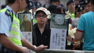 A woman holds banners denouncing China's government and the detention of mainland dissidents, during a protest outside the Chinese liaison office in Hong Kong on April 3, 2011