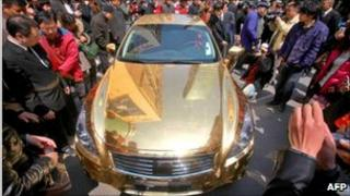 Crowd gathers to admire a gold-plated Infiniti luxury sports car in Beijing