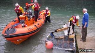 Looe lifeboat with retrieved section of the Norvik. Pic: Looe RNLI