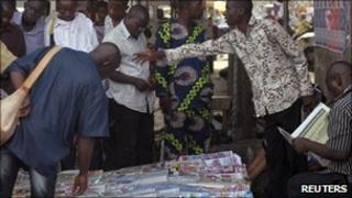 Men gather at a newspaper vendor's stall in Lagos, Nigeria