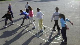 Primary school children playing hopscotch in a playground
