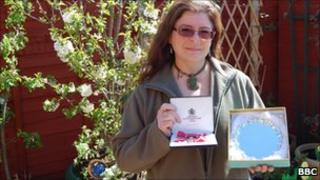 Jo Wood in her garden with her MBE and her Cheshire Woman of the Year plaque