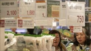 Customers buy vegetables at a store in Seoul
