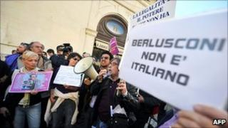 People protest outside Italy's lower house of parliament in Rome, 13 April 2011