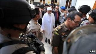 Armed anti-terror police commandos escort Abu Bakar Ba'asyir at Jakarta court on March 14, 2011