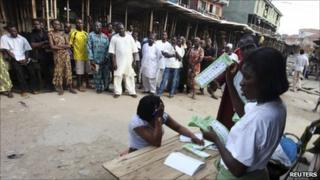 "An electoral officer counts ballots as people watch at the end of the parliamentary elections in Oshodi district in Nigeria""s commercial capital of Lagos April 9, 2011"