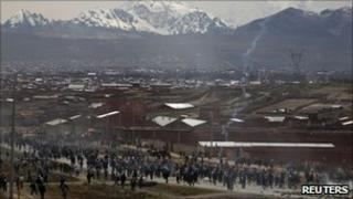 Protesters run from tear gas on a road outside La Paz, Bolivia