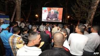 Algerians gather to watch President Bouteflika's speech on a giant screen in Telemcen, 15 April