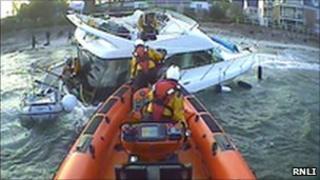 Lifeboat helping sinking motorboat