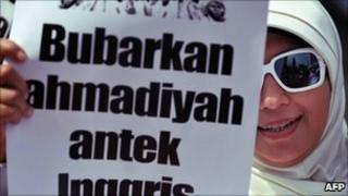 """A protester hold a placard reading """"Disband Ahmadiyah, British stooge"""" at an anti-Ahmadiyah rally in Jakarta on 18 February 2011"""