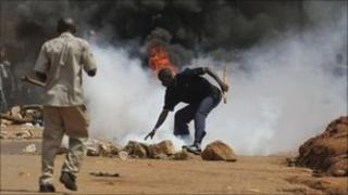 A Ugandan protester reaches down to pick up a tear gas grenade that police fired at a crowd in Kampala - 18 April 2011