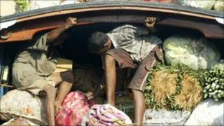 Sri Lanka workers unload vegetables from a lorry in the capital, Colombo