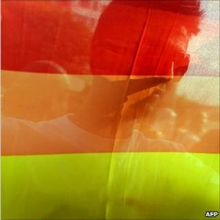 A man is seen behind a gay pride rainbow flag