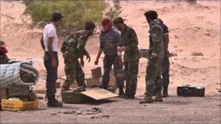 Libyan rebels unpack land-mines before laying them near Ajdabiya, 17 April