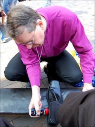 The Bishop of Southwell and Nottingham, the Rt Revd Paul Butler shine shoes in Nottingham city centre