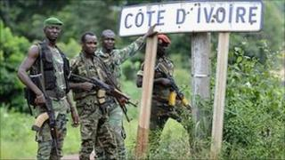 Pro-Ouattara militiamen pose beside a road sign on the border with Liberia. 20 April 2011