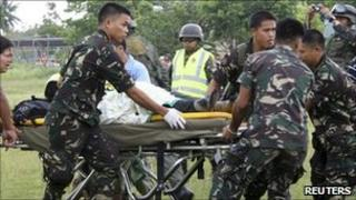 Soldiers carry a survivor on a stretcher in Kingking village, southern Philippines, on 22 April 2011