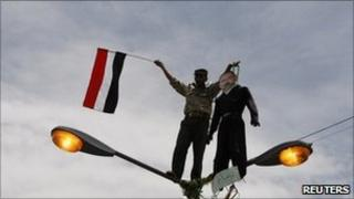 A protester holds a flag and an effigy of Yemeni President Ali Abdullah Saleh while standing on a lamp-post in the Yemeni capital Sanaa, 23 April